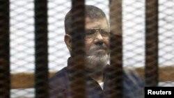 무함마드 무르시 전 이집트 대통령이 지난해 6월 카이로 외곽의 법원에서 자신의 판결 내용을 듣고 있다.