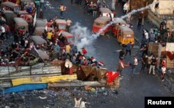 28일 이라크 바그다드에서 반정부 시위가 열린 가운데 시위참가자들이 경찰을 발포한 최루탄을 피해 흩어지고 있다.