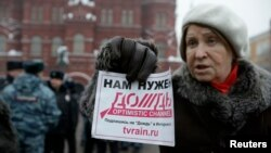 "FILE - A protester holds a flyer reading ""We need Dozhd"" during a rally in support of the independent television station Dozhd (TV Rain), in Moscow, February 8, 2014."