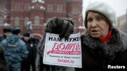 """2014年2月8日,一名參加抗議活動人士手拿標語支持""""雨電視"""" 。"""