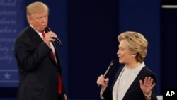 Republican presidential nominee Donald Trump and Democratic presidential nominee Hillary Clinton speak during the second presidential debate at Washington University in St. Louis, Oct. 9, 2016.