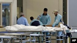 Medical personnel examine a body at the Orlando Medical Examiner's Office, June 12, 2016, in Orlando, Florida. A gunman opened fire inside a crowded gay nightclub early Sunday, before being killed in a gunfight with SWAT officers, police said.