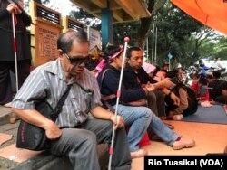 Seorang penyandang disabilitas netra berteduh dalam tenda yang didirikan mahasiswa disabilitas setelah diputus layanan oleh Asrama Wyata Guna, Bandung, Rabu (15/1/20) sore. (VOA/Rio Tuasikal)