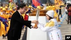 2018 평창동계올림픽 개막을 100일 앞둔 1일 한국 인천대교에서 열린 성화봉송식에서 이낙연 국무총리가 첫번째 봉송 주자인 여자 피겨 유영 선수에게 성화를 전달하고 있다.