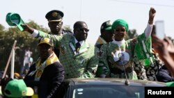 Zimbabwean President Robert Mugabe (C) and his wife Grace wave to supporters at an election rally in Chitungwiza, about 35 kilometers south of the capital Harare, July 16, 2013.
