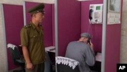북한에 억류돼 6년 노동교화형을 선고받은 미국인 매튜 토트 밀러 씨(오른쪽)가 24일 북한 교도관이 지켜보는 가운데 가족과의 전화 통화를 하고 있다.