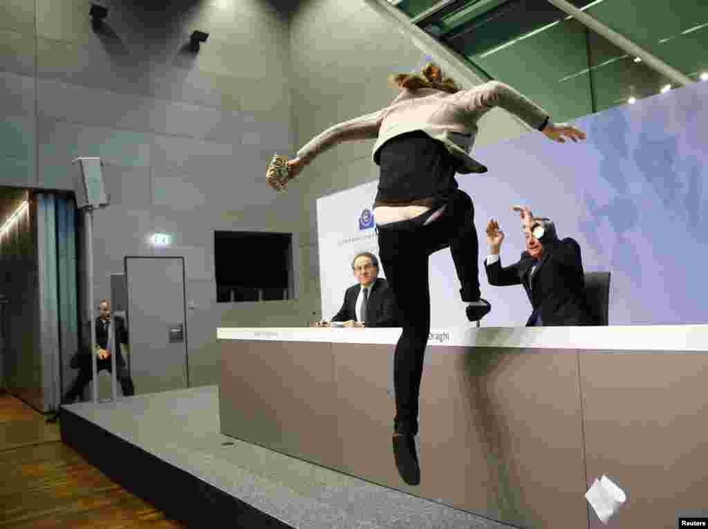A protester jumps on the table in front of the European Central Bank President Mario Draghi during a news conference in Frankfurt, Germany.