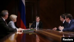 FILE - Russian Prime Minister Dmitry Medvedev (C) chairs a meeting at the Gorki state residence outside Moscow as Russia and China aim to wrap up 10 years of talks about Russian gas supplies