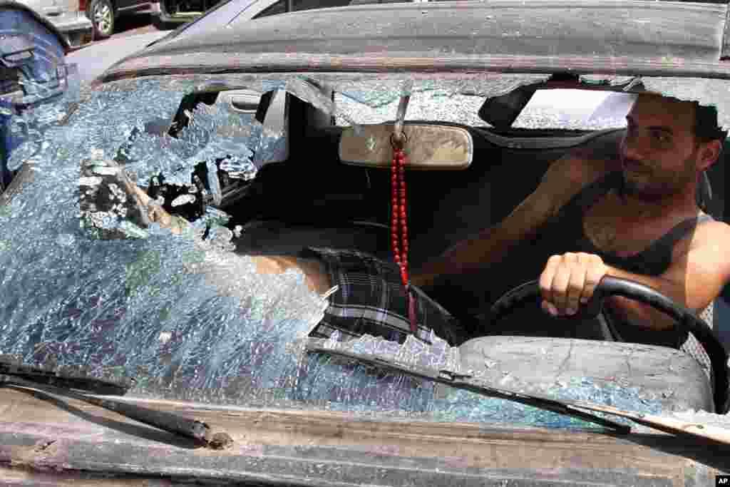 Libanac iz Sisona razbija i uklanja ostatke šoferšajbe na oštećenom automobilu.