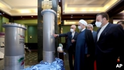 Foto ini dirilis oleh situs resmi kantor kepresidenan Iran, Presiden Iran Hassan Rouhani, kedua dari kanan, mendengarkan kepala Organisasi Energi Atom Iran Ali Akbar Salehi, 10 April 2021. (Foto: AP)