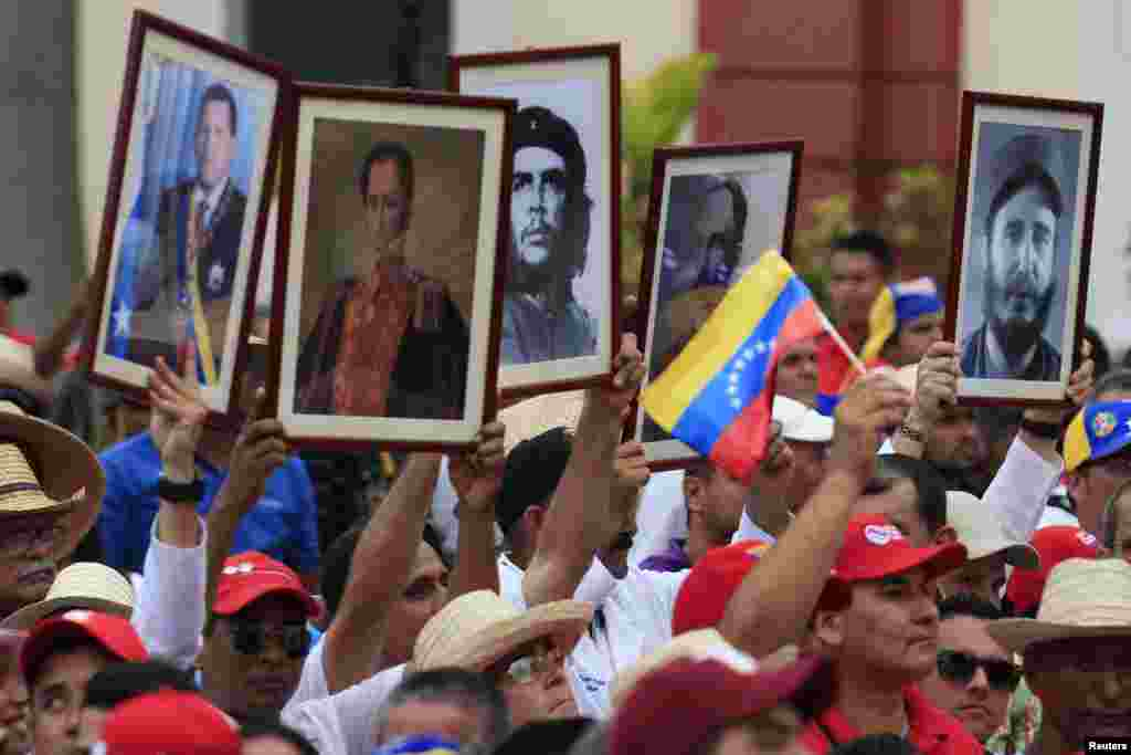 Cuban doctors hold up framed pictures (L-R) of late president Hugo Chavez, Venezuela's National hero Simon Bolivar, Ernesto 'Che' Guevara, Cuban national hero Jose Marti and Fidel Castro during a march of farmers in support of Venezuelan President Nicolas Maduro, Caracas, Feb. 26, 2014.