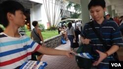 普教中學生關注組副主席網名「郭奉孝」(左)向香港市民派發反對普教中傳單。(美國之音湯惠芸)