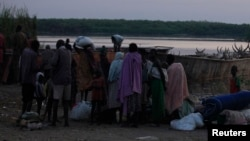People displaced by fighting in Bor county stand by their belongings after arriving in the port of Minkaman, Awerial county, Lakes state, South Sudan, Jan. 14, 2014.