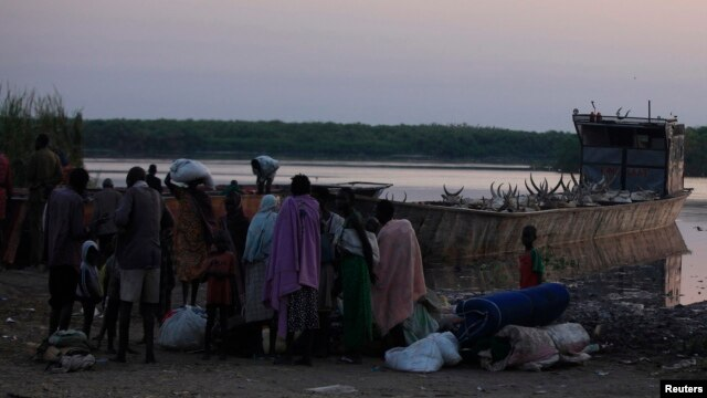 People displaced by the fighting in Bor county, stand by their belongings after arriving in the port of Minkaman, in Awerial county, Lakes state, in South Sudan, Jan. 14, 2014.