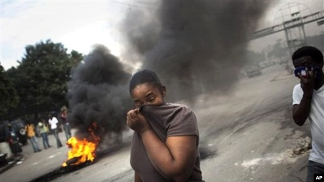 A woman covers her face from the smoke of burning tires set up by demonstrators in Port-au-Prince, Haiti,  15 Nov. 2010.