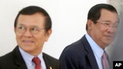 File photo - Cambodia's Prime Minister Hun Sen, right, walks with opposition Cambodia Rescue Party Deputy President Kem Sokha, left, during a break at National Assembly in Phnom Penh, Cambodia, Wednesday, Dec. 7, 2016.