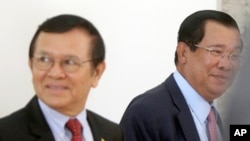 Cambodia's Prime Minister Hun Sen, right, walks with opposition Cambodia Rescue Party Deputy President Kem Sokha, left, during a break at National Assembly in Phnom Penh, Cambodia, Wednesday, Dec. 7, 2016. Cambodia's newly pardoned Kem Sokha has returned to parliament with a claim that he and Prime Minister Hun Sen have agreed to help reconcile their contending parties for the sake of benefiting the country. (AP Photo/Heng Sinith)