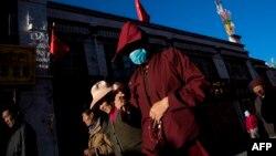 在中國西藏自治區首府拉薩,一名僧侶走在大昭寺外誦經。 (2016年9月10日)