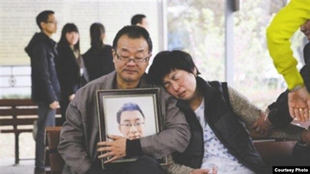 魏则西的父母手捧着魏则西的遗像(网络图片)