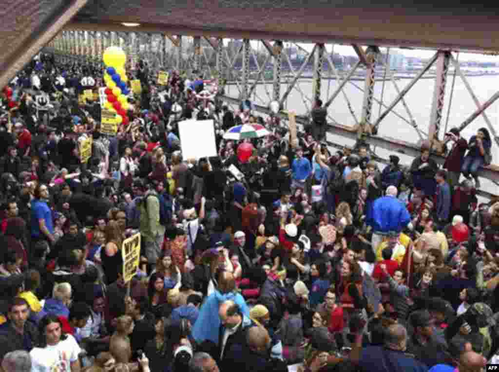 A large group of protesters affiliated with the Occupy Wall Street movement attempt to cross the Brooklyn Bridge, effectively shutting parts of it down, Saturday, Oct. 1, 2011 in New York. Police arrested dozens while trying to clear the road and reopen f