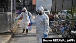 Petugas Kesehatan Darurat menyemprotkan cairan disinfektan di sebuah kawasan di Wuhan, China di tengah merebaknya wabah corona virus, 30 Januari 2020. (Foto: AFP)