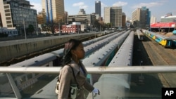 A Johannesburg resident walks on Mandela Bridge over railroad tracks in Johannesburg, South Africa, June 29, 2006.