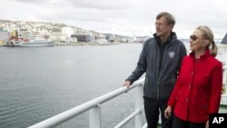 US Secretary of State Hillary Rodham Clinton, right, speaks with Jarle Aarbakke, Rector of the University of Tromso, aboard the Arctic Research Vessel Helmer Hanssen during a boat tour of the coastline with Norway's Minister of Foreign Affairs Jonas Gahr