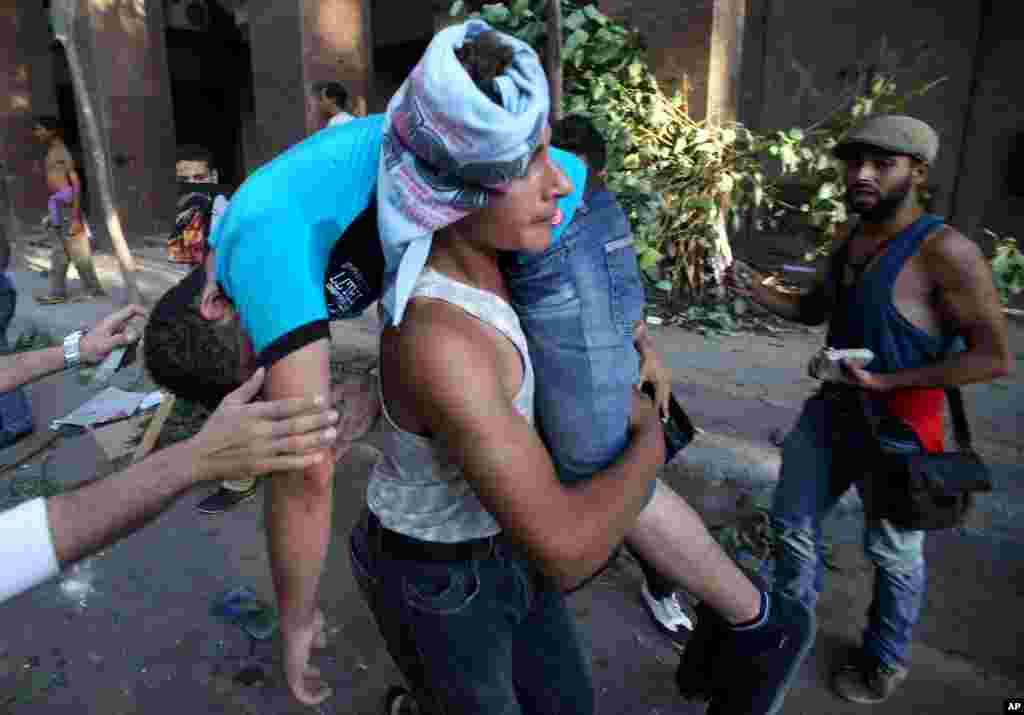 An opponent of ousted President Mohamed Morsi carries a wounded friend during clashes with Morsi supporters, in Cairo, July 22, 2013.