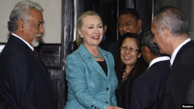 U.S. Secretary of State Hillary Clinton (C) shakes hands with staff members next to East Timor's Prime Minister Xanana Gusmao (L) at the Prime Minister's office in Dili September 6, 2012.