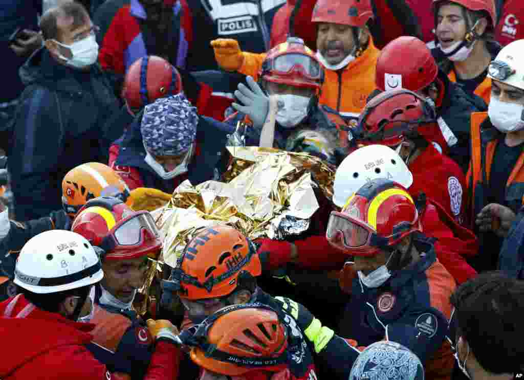 Elif Perincek, a three-year-old survivor, holds the thumb of a rescue worker as she is rescued from the rubble of a building some 65 hours after a magnitude 6.6 earthquake in Izmir, Turkey. (Istanbul Fire Authority/Handout)