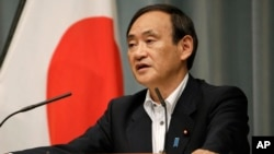 FILE - Japan's Chief Cabinet Secretary Yoshihide Suga answers a question from a journalist during a press conference at the prime minister's official residence in Tokyo, Sept. 30, 2015. Japan has moved up the launch of an anti-terrorism intelligence unit following the deadly attacks in Paris.