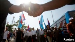 Sam Rainsy (C), leader of the opposition Cambodia National Rescue Party (CNRP), marches during International Human Rights Day in Phnom Penh, Dec. 10, 2013.