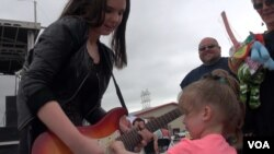 One of Ally's young fans takes a turn on her guitar. (G. Flakus/VOA)