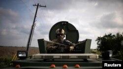 무장한 미 국경순찰대 전술부대(BORTAC) 관계자가 지난 8일 멕시코 접경 도시 텍사스주 미션에서 훈련을 위해 장갑차를 타고 있다.