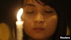 Una mujer ora por las 239 personas desaparecidas en el vuelo de la aerolínea Malaysia Airlines. Otras vigilias se llevan a cabo en Kuala Lumpur.