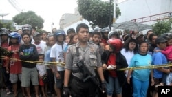 A policeman stands guard as residents watch the site of an explosion in front of a church in Solo, Central Java September 25, 2011.