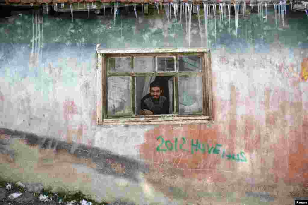 A man watches the street from a window as icicles hang from the roof of his house in the Hacibayram district of Ankara, Turkey.  Storms this week brought blizzards, rain and plummeting temperatures to the Middle East.