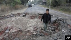 A Thai man walks though a bomb crater near Sisaket, Thailand, near the border with Cambodia, Monday, Feb. 7, 2011. Troops of Cambodia and Thailand continue to clash near the 11th century Preah Vihear temple.