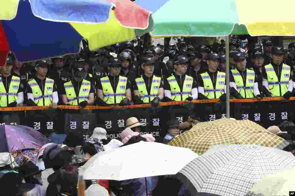Evangelical Baptist Church believers sit as police officers searching for a fugitive billionaire businessman over April's ferry sinking stand in line in font of the main gate of the church in Anseong, South Korea, June 11, 2014.