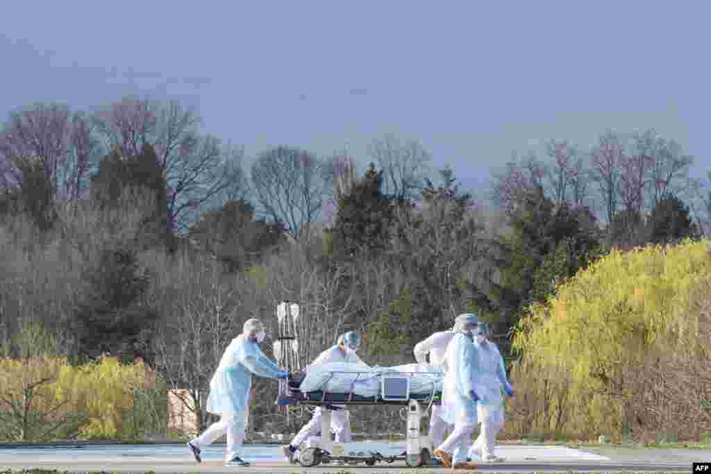 Medical workers push a patient to a waiting medical helicopter at the Emile Muller hospital in Mulhouse, eastern France, during the coronavirus pandemic.