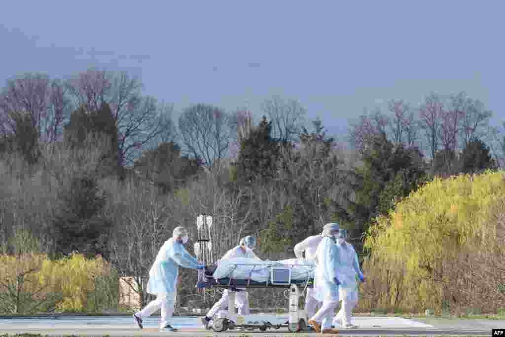 Fransanın şərqində Emile Muller hospitalının tibb içşiləri pasienti xərəkdə tibbi helikopterə aparır.