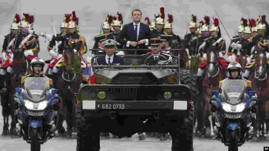 Le nouveau président français Emmanuel Macron monte dans un véhicule militaire dans la parade à Paris, en France, le 14 mai 2017.