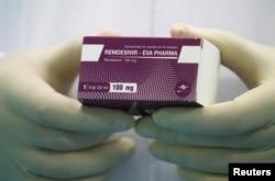 """Seorang teknisi laboratorium memperlihatkan kotak obat """"Remdesivir"""" di Eva Pharma Facility, Kairo, Mesir 25 Juni 2020. (REUTERS/Amr Abdallah Dalsh)"""