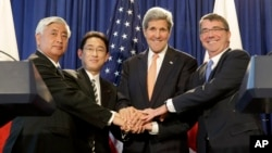 From left, Japanese Defense Minister Gen Nakatani, Japanese Foreign Minister Fumio Kishida, Secretary of State John Kerry, and Defense Secretary of Defense Ash Carter pose for a picture during a news conference in New York, Monday, April 27, 2015. The US and Japan are boosting their defense relationship, allowing Japan to play a bigger role in global military operations with an eye on potential threats from China and North Korea. (AP Photo/Seth Wenig))