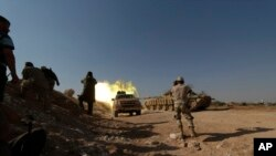 FILE - Free Syrian Army fighters fire from a tank during offensive to take control of al-Zaalana checkpoint in Wadi al-Deif military camp, southern Idlib countryside, July 9, 2014.
