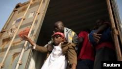 Un homme aide une personne aveugle à descendre d'un camion à la frontière du Cameroun et de la Centrafrique, le 8 mars 2014.