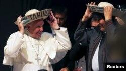 """El papa Francisco y el presidente Evo Morales se colocan sombreros típicos de sao, el típico de los cruceños, con la palabra """"Tahuichi"""" que es el nombre indio de un pájaro."""