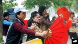 Vietnamese women perform fan dancing along the shores of Hoan Kiem Lake in Hanoi, Vietnam.