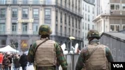 Les forces de sécurité patrouillent devant la Bourse de Bruxelles ou les gens se recueillent publiquement le 23 mars 2016, Bruxelles, Belgique.