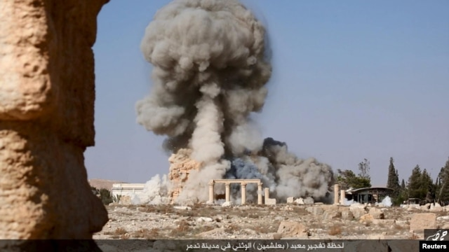FILE - An image distributed by Islamic State militants on social media on Aug. 25, 2015, purports to show the destruction of a Roman-era temple in the ancient Syrian city of Palmyra.